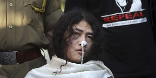 FILE – In this March 4, 2013 file photo, an Indian policeman, left, and a supporter stand behind India's most famous prisoner of conscience Irom Sharmila, who has been on a hunger strike for 12 years to protest an Indian law that suspends many human rights protections in areas of conflict, during a press conference, in New Delhi, India. India's government has decided to decriminalize suicide attempts, which earlier were punishable by up to a year in prison, a crime for which Sharmila has been in judicial custody for years. Junior Home Minister Haribhai Parathibhai Chaudhary told Parliament on Wednesday, Dec. 10, that if a person attempts suicide and survives, he or she will no longer be treated as a criminal, with the government removing Section 309 of the Penal Code from the statute book. (AP Photo/Tsering Topgyal, File)