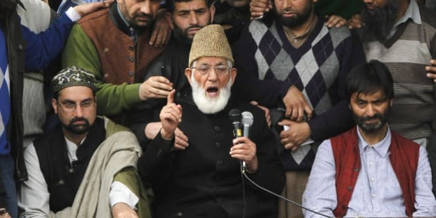 Kashmiri separatist leader Syed Ali Geelani flanked by separatist leaders Yasin Malik, right, and Mirwaiz Umar Farooq, left, speaks during a joint protest against the killing of a teenage boy in Narbal, some 15 Kilometers (10 miles) west of Srinagar, Indian-controlled Kashmir, Monday, April 20, 2015. Relatives and witnesses have contested the official story of the boy's death, saying he had been picked up by authorities and was shot on the side of the road while in custody. Police said in a statement that they arrested two policemen after a preliminary investigation. (AP Photo/Mukhtar Khan)