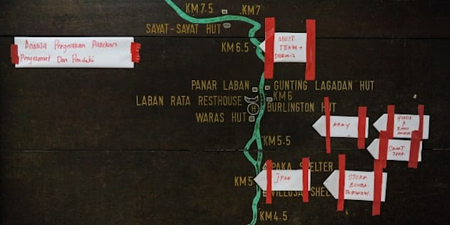 Pieces of paper showing various Malaysian rescue teams mark their current positions on a summit trail information board, heading towards Mount Kinabalu, at the Timpohon gate checkpoint a day after an earthquake in Kundasang, a town in the district of Ranau on June 6, 2015.  Malaysian rescuers brought 137 hikers down to safety on June 6 after an earthquake had stranded them atop Mount Kinabalu, but reports said at least two people were killed and 16 remained missing.      AFP PHOTO / MOHD RASFAN        (Photo credit should read MOHD RASFAN/AFP/Getty Images)