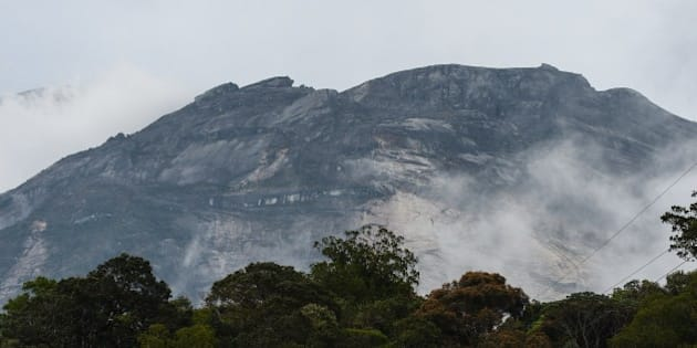 Malaysia's Mount Kinabalu is seen among mists from the Timpohon gate check point a day after the earthquake in Kundasang, a town in the district of Ranau on June 6, 2015.  A strong earthquake that jolted Malaysia's Mount Kinabalu killed at least 11 people and left another 8 missing, an official said, as authorities continued to search for survivors on Southeast Asia's highest peak.     AFP PHOTO / MOHD RASFAN        (Photo credit should read MOHD RASFAN/AFP/Getty Images)