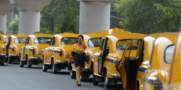 An Indian pedestrian walks past parked taxis in Kolkata on May 25, 2015.  More than 430 people have died in two Indian states from a days-long heatwave that has seen temperatures nudging 50 degrees Celsius (122 degrees Fahrenheit), officials said May 25. In the eastern city of Kolkata, taxi unions have urged drivers to stay off the roads between 11am and 4pm because of the heat. AFP PHOTO/ Dibyangshu Sarkar        (Photo credit should read DIBYANGSHU SARKAR/AFP/Getty Images)