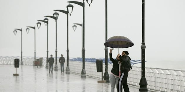 A Lebanese couple takes a selfie under the rain as they walk at Beirut's seaside corniche in Ain al-Mreisseh during a heavy storm on February 11, 2015. A fierce sandstorm lashed Egypt, Israel and Lebanon closing the Suez Canal to ships and grounding domestic flights in Israel.   AFP PHOTO/JOSEPH EID        (Photo credit should read JOSEPH EID/AFP/Getty Images)