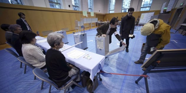 A representative of a local election administration commission shows the earliest two voters the empty ballot box before they cast their votes for parliament's lower house election at a polling station in Tokyo, Sunday, Dec. 14, 2014. Japanese voters headed to the polls Sunday in a parliamentary election that is expected to reaffirm the ruling Liberal Democratic Party's majority, though many analysts were predicting a record low turnout. (AP Photo/Eugene Hoshiko)