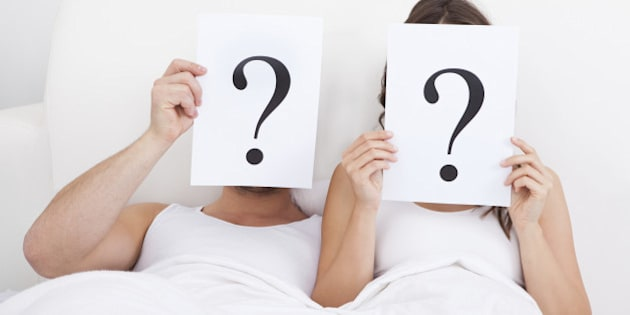 Couple Lying On Bed Holding Question Mark On Face