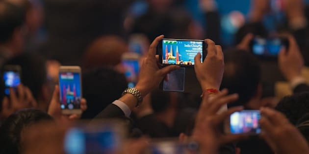 India's Prime Minister Narendra Modi is seen on mobile phone screens while he delivers a speech at the India-China Business Forum in Shanghai on May 16, 2015.  Indian and Chinese firms signed 21 agreements officials said were worth a total of more than 22 billion USD witnessed by visiting Prime Minister Narendra Modi.     AFP PHOTO / JOHANNES EISELE        (Photo credit should read JOHANNES EISELE/AFP/Getty Images)