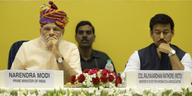 Indian Prime Minister Narendra Modi, left, sits with junior Minister for Information and Broadcasting Rajyavardhan Singh Rathore at  the launch of a special television channel for farmers in New Delhi, India, Tuesday, May 26, 2015. Modi's government is marking their first year in office Tuesday. (AP Photo/ Manish Swarup)