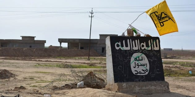 A flag of the Shiite Hezbollah militant group flutters over a mural depicting the emblem of the Islamic State (IS) group in Al-Alam village, northeast of the multi-ethnic Iraqi city of Tikrit, on March 9, 2015, during a military operation by Iraqi government forces and tribal fighters to regain control of the Tikrit region from jihadists. After being forced out of the province of Diyala earlier this year, the IS jihadists are now fighting off a huge assault on the city of Tikrit as government and allied forces continue to work their way north towards the main IS stronghold of Mosul. AFP PHOTO / YOUNIS AL-BAYATI        (Photo credit should read YOUNIS AL-BAYATI/AFP/Getty Images)