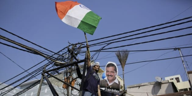 "A supporter of the Aam Aadmi Party, or Common Man's Party, waves the Indian flag next to a portrait of its leader Arvind Kejriwal and party symbol, broom, as he celebrates party's victory in New Delhi, India, Tuesday, Feb. 10, 2015. The upstart anti-corruption party has won a smashing victory in elections to install a state government in India's capital, officials said Tuesday, dealing a huge blow to Prime Minister Narendra Modi's Hindu nationalist party. Hindi below the portrait reads, ""five years Kejriwal"".(AP Photo/Altaf Qadri)"