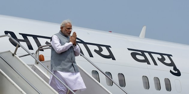 Indian Prime Minister, Narendra Modi gives a traditional greeting as he exits the plane on his arrival at the Hazrat Shahjalal International Airport in Dhaka on June 6, 2015.  India's prime minister arrived in Bangladesh to seal a land pact which will finally allow tens of thousands of people living in border enclaves to choose their nationality after decades of stateless limbo.  AFP PHOTO/ Munir uz ZAMAN        (Photo credit should read MUNIR UZ ZAMAN/AFP/Getty Images)