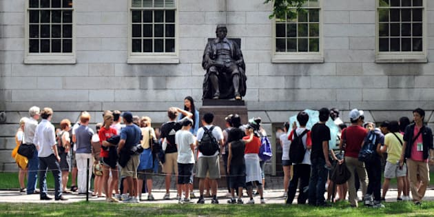 CAMBRIDGE, MA - JULY 30: People touring Harvard Yard stop by the John Harvard statue July 30, 2009 just off Harvard Square in Cambridge, Massachusetts. Harvard Square is a large triangular area located in the heart of Cambridge and adjacent to Harvard University, and is frequented by tens of thousands of tourists a year, and home to thousand of students with MIT University just down the road. (Photo by Darren McCollester/Getty Images)