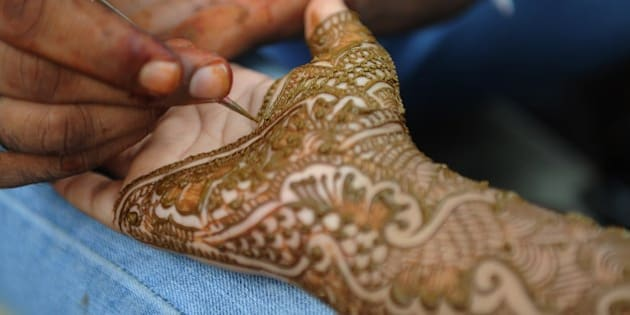 An Indian Muslim woman gets her hands decorated with traditional henna designs at a roadside stall ahead of the Muslim festivities of Eid al-Fitr, in Mumbai on July 28, 2014. Muslims around the world are preparing to celebrate the Eid al-Fitr holiday, which marks the end of the fasting month of Ramadan.  AFP PHOTO/ INDRANIL MUKHERJEE        (Photo credit should read INDRANIL MUKHERJEE/AFP/Getty Images)