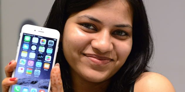 An Indian customer poses with her brand new Apple iPhone 6 at the Unicorn Infosolutions Apple Premium Reseller store in Ahmedabad early on October 17, 2014.  Apple launched the iPhone 6 and iPhone 6 Plus smartphones in India at midnight on October 17.  AFP PHOTO / Sam PANTHAKY        (Photo credit should read SAM PANTHAKY/AFP/Getty Images)