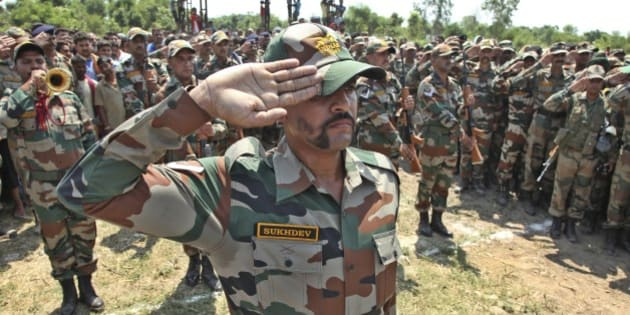 Indian army soldiers pay tribute to their colleague Randeep Singh, who was killed in Thursday's rebel attack in northeastern Manipur state after his body was brought to Akhnoor, Jammu and Kashmir state, India, Sunday, June 7, 2015. A group of rebels using rocket-propelled grenades and automatic weapons ambushed a military convoy in India's insurgency-wracked northeast on Thursday, killing more than a dozen soldiers in the latest major attack in the region in recent months. (AP Photo/Channi Anand)