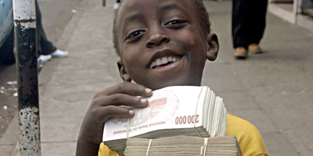 A child poses with wads of Zimbabwean dollar notes begged on the streets of Harare Tuesday, Feb. 19, 2008. The official rate of annual inflation in Zimbabwe rocketed past the 100,000 percent barrier, by far the highest in the world, the state central statistical office said Thursday Feb 21, 2008. (AP Photo)