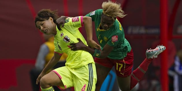 Japan defender Saki Kumagai (L) and Cameroon forward Gaelle Enganamouit fight for the ball during a Group C football match between Japan and Cameroon at BC Place Stadium in Vancouver British Columbia during the FIFA Women's World Cup Canada 2015 on June 12, 2015.   AFP PHOTO/ANDY CLARK        (Photo credit should read ANDY CLARK/AFP/Getty Images)