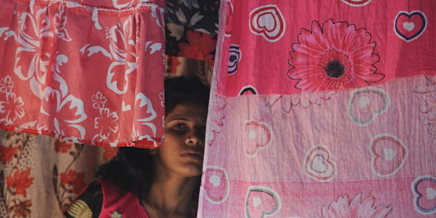 An Indian sex worker looks on past curtains in the red light district of Kamathipura in Mumbai on August 23, 2010, ahead of the Hindu festival of 'Raksha Bandhan'. Prostitution is illegal in India but police often turn a blind eye to the trade. There are around 1.2 million sex workers in the country, according to the National AIDS Control Organisation. AFP PHOTO/ Punit PARANJPE (Photo credit should read PUNIT PARANJPE/AFP/Getty Images)