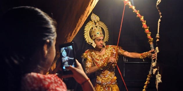 An Indian woman takes a photograph on her mobile of an artist dressed as Lord Rama as he waits backstage prior to a performance of the Ramlila, a dramatisation of Hindu God Rama's life, in Jammu on September 25, 2013. Ramlila is a dramatic folk re-enactment of the life of Lord Rama's victory after a ten day battle with the ten headed Demon King Ravana, as described in the Hindu religious epic, the Ramayana.  AFP PHOTO        (Photo credit should read STR/AFP/Getty Images)