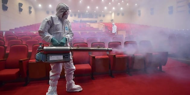South Korean health officials fumigate a theater while wearing protective gear in Seoul on June 12, 2015. South Korea on June 12, reported four more cases of Middle East Respiratory Syndrome (MERS), bringing to 126 the total number of people diagnosed with the potentially deadly virus. AFP PHOTO / JUNG YEON-JE        (Photo credit should read JUNG YEON-JE/AFP/Getty Images)