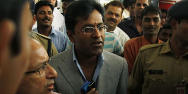 Suspended Indian Premier League Chairman Lalit Modi, center, is surrounded by bodyguards, media, and onlookers as he arrives at the airport from a flight in New Delhi, India, Wednesday, April 28, 2010. Modi was suspended Sunday and is under investigation on allegations of corruption dating back to the IPL's  inaugural season in 2008. (AP Photo/Saurabh Das)