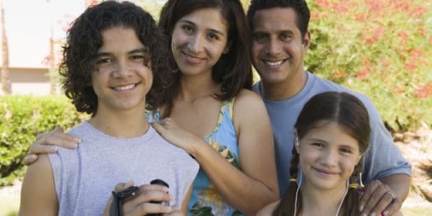 Boy (13-15) holding camcorder, standing outdoors with sister (7-9) and parents, portrait.