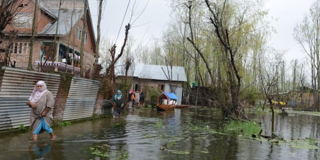 Kashmiri residents walk through floodwaters outside their homes as water levels rise on Dal Lake in Srinagar on April 1, 2015. Many low lying areas in Indian Kashmir were flooded for the second time since September last year. On March 30, fifteen members of two families including a three-week old baby died after they were buried alive by a landslide caused by incessant rains flooding in the region. But officials sounded hope as water levels in River Jhelum, that causes the biggest threat of flooding in Srinagar, continued to decrease. AFP PHOTO/Tauseef MUSTAFA        (Photo credit should read TAUSEEF MUSTAFA/AFP/Getty Images)