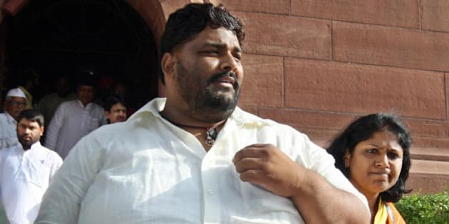 Member of Parliament from India's Rashtriya Janata Dal (RJD) Pappu Yadav (L), who is serving a life sentence in New Delhi's Tihar jail on charges of murdering a Communist Party of India-Marxist leader, walks towards parliament house in New Delhi on July 22, 2008.   India's embattled coalition government will go into a parliamentary confidence vote with a tiny advantage but the margin is so tight it has no guarantee of surviving, Indian media say. The Congress party-led coalition government requires a simple majority to survive the vote after its left-wing allies withdrew support earlier this month over their opposition to a nuclear energy agreement with the United States. AFP PHOTO/Prakash SINGH (Photo credit should read PRAKASH SINGH/AFP/Getty Images)