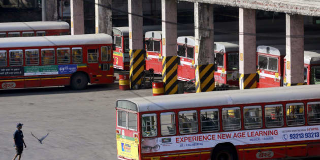 A man walks past parked buses at a station during a bus strike in Mumbai, India, Wednesday, April 2, 2014. Local transport was affected as bus drivers and assistants of the Brihanmumbai Electric Supply and Transport (BEST) continued their strike for a second day to protest the new computerized scheduling system. (AP Photo/Rafiq Maqbool)
