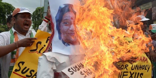 Congress supporters shout anti-Bharatiya Janata Party (BJP) slogans as they burn effigies of External Affairs Minister, Sushma Swaraj and  former cricket administrator, Lalit Modi during a protest in Kolkata on June 17, 2015.   Congress ramped up its demand for the resignation of Rajasthan chief minister, Vasundhara Raje and External Affairs Minister, Sushma Swaraj a day after controversial former Indian Premier League (IPL) boss Lalit Modi claimed they helped him with his travel papers in Britain.    AFP PHOTO/ Dibyangshu SARKAR        (Photo credit should read DIBYANGSHU SARKAR/AFP/Getty Images)