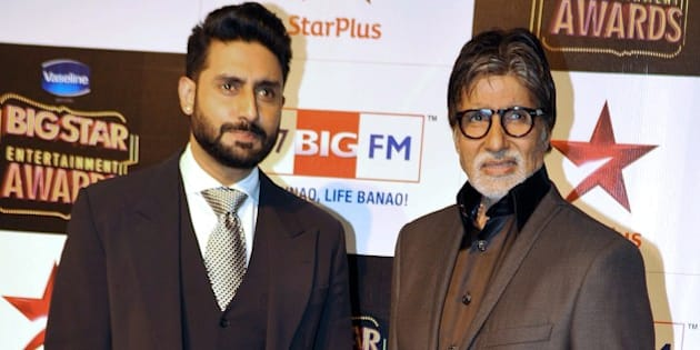 Indian Bollywood film actors Abhishek Bachchan (L) and Amitabh Bachchan attend the 'BIG Star Entertainment Awards' ceremony in Mumbai on December 18, 2014.  AFP PHOTO        (Photo credit should read STR/AFP/Getty Images)