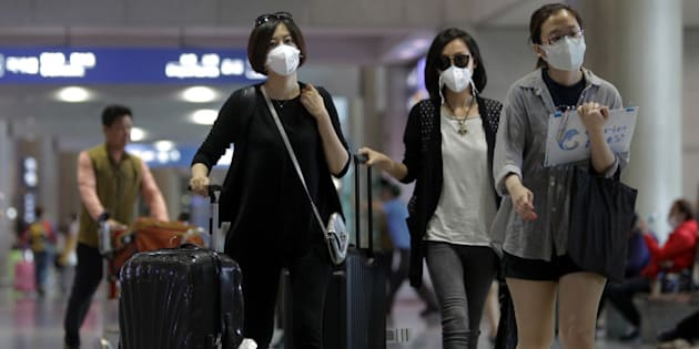 INCHEON, SOUTH KOREA - JUNE 06:  Tourists wear masks as a precaution against the MERS virus at the Incheon International Airport on June 6, 2015 in Incheon, South Korea. Four deaths from Middle East Respiratory Syndrome (MERS) have been confirmed on June 5, 2015, and the number of confirmed local patients have risen to fifty as of June 6, 2015.  (Photo by Chung Sung-Jun/Getty Images)