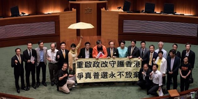 Hong Kong pro-democracy lawmakers display a banner after a vote at the city's legislature in Hong Kong on June 18, 2015. Hong Kong lawmakers rejected a Beijing-backed political reform package on June 18 as pro-democracy legislators united to vote down the divisive electoral roadmap that has sparked mass protests. AFP PHOTO / Philippe Lopez        (Photo credit should read PHILIPPE LOPEZ/AFP/Getty Images)