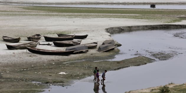 Indian children play near parked boats on the banks of river Ganges where water level has dried up in the summer in Allahabad, India, Wednesday, June 3, 2015. Light to moderate rainfall in various parts of the country brought respite from the scorching sun but heat wave claimed many lives in the southern Indian states of Andhra Pradesh and Telangana, raising the overall death toll to more than 2,000 since mid-April. (AP Photo/Rajesh Kumar Singh)