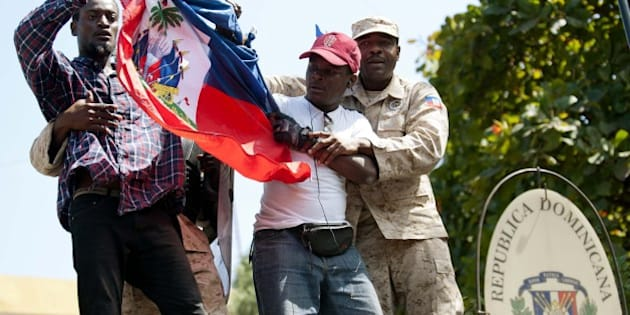 Haitian police  remove protestors who tried to place the Haitian flag on the mast of the Consulate General of the Dominican Republic during a demonstration in Port-au-Prince on February 25, 2015, calling for the end of what protestors said was anti-Haitian sentiment in the Dominican Republic. The demonstrators also called for nonviolence and the end of racism. On February 10, a Haitian immigrant in the Dominican Republic was found hanged, reportedly lynched, from a tree in a park in Santiago. AFP PHOTO/ HECTOR RETAMAL        (Photo credit should read HECTOR RETAMAL/AFP/Getty Images)