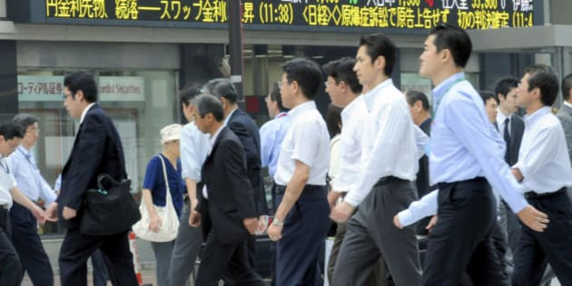 Businessmen cross an intersection,  with stock prices seen on an electric market board in Tokyo, Wednesday, June 11, 2008. Japan raised its reading for economic growth in the first quarter, due mainly to a stronger-than-expected increase in capital investment. (AP Photo/Katsumi Kasahara)