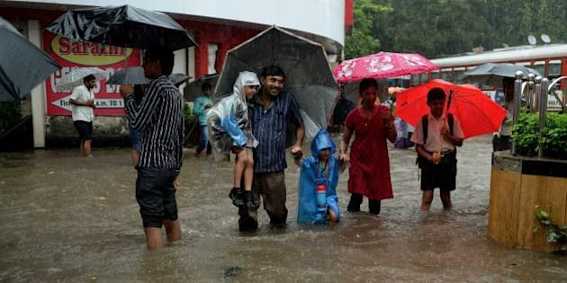 Indians walk through a flooded street during rain showers in Mumbai on July 23, 2013. The Mumbai city witnessed heavy rains on Tuesday, resulting in heavy traffic jams and disrupting train services. The monsoon season, which runs from June to September, accounts for about 80 percent of India's annual rainfall, vital for a farm economy which lacks adequate irrigation facilities.  AFP PHOTO/ PUNIT PARANJPE        (Photo credit should read PUNIT PARANJPE/AFP/Getty Images)