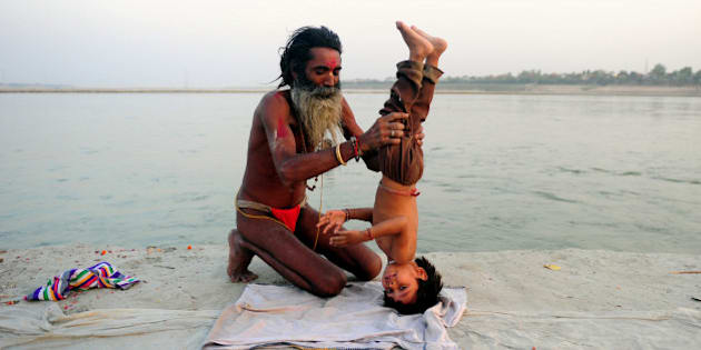 An Indian Hindu Sadhu (holy man) poses his adopted child in a yoga headstand on the banks of the Sangam in Allahabad on April 30, 2013.  Yoga, which means union in Sanskrit, is a family of ancient spiritual practices and also a school of spiritual thought from the Asian subcontinent, where it remains a vibrant living tradition and is seen as a meaning of enlightenment. AFP PHOTO/ SANJAY KANOJIA        (Photo credit should read Sanjay Kanojia/AFP/Getty Images)