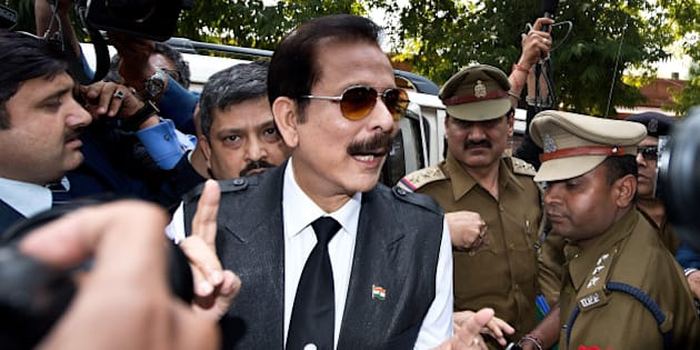 India's Sahara group chairman Subrata Roy (C) speaks to the media as he arrives at the Supreme Court in New Delhi on March 4, 2014.  Black ink was thrown on Sahara chairman Subrata Roy's face as he arrived at the Supreme Court , escorted by police personnel. The attacker, who managed to get close to Roy in the crowd and threw black ink on him, claimed to be Manoj Sharma, a lawyer from Gwalior, Madhya Pradesh.  Roy was arrested after he failed to respond to the Supreme Court's summons to appear in court in connection with the case in which Sahara owes millions of investors over 22,000 crore Indian rupees (3.5 billion dollars). AFP PHOTO/Prakash SINGH        (Photo credit should read PRAKASH SINGH/AFP/Getty Images)