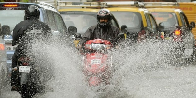 An Indian motorcyclist rides along a flooded street after heavy rain in Mumbai on July 16, 2014. The monsoon rains, which usually hit India from June to September, are crucial for farmers whose crops feed hundreds of millions of people. AFP PHOTO/ PUNIT PARANJPE         (Photo credit should read PUNIT PARANJPE/AFP/Getty Images)