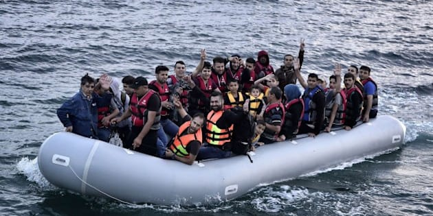 Syrian refugees flash the victory sign as they sit aboard a dinghy carrying heading to the island of Lesbos early on June 18, 2015. Some 48,000 migrants and refugees have landed on Greek shores so far this year, compared to 34,000 arrivals during all of 2014, according to the International Organization for Migration (IOM). AFP PHOTO / LOUISA GOULIAMAKI        (Photo credit should read LOUISA GOULIAMAKI/AFP/Getty Images)