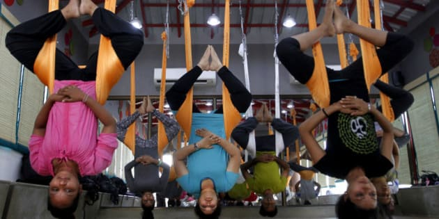 In this Thursday, June 18, 2015, photo, Indians perform anti gravity aerial yoga in Ahmadabad, India. Yoga has a long history India, reaching back for thousands of years. The government of Prime Minister Narendra Modi has made clear it wants the first International Yoga Day, held on Sunday, June 21, 2015, to be taken seriously. (AP Photo/Ajit Solanki)