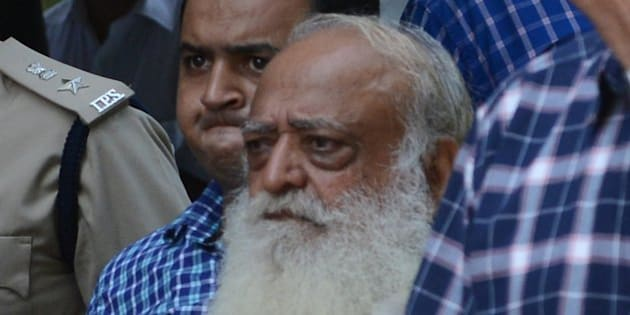 Indian spiritual guru Asaram Bapu (C, in white) is escorted by state police as he arrives at a local court in Gandhinagar, some 30 kms. from Ahmedabad, on October 15, 2013. The court ordered the spiritual guru to be under police custody until October 19 in connection with a sexual assault case. AFP PHOTO / Sam PANTHAKY        (Photo credit should read SAM PANTHAKY/AFP/Getty Images)
