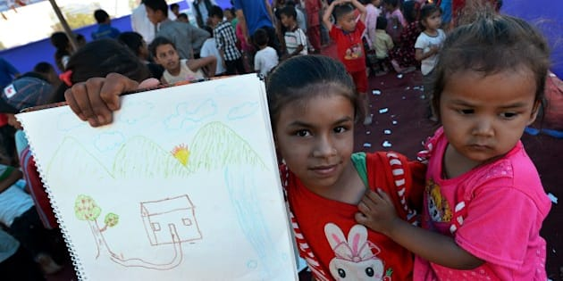 A Nepalese child holds up a drawing at a relief camp for survivors of the Nepal earthquake in Kathmandu on May 23, 2015. Nearly 8,500 people have now been confirmed dead in the disaster, which destroyed more than half a million homes and left huge numbers of people without shelter with just weeks to go until the monsoon rains. AFP PHOTO / ISHARA S. KODIKARA        (Photo credit should read Ishara S.KODIKARA/AFP/Getty Images)