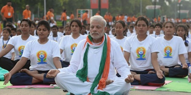 Indian Prime Minister Narendra Modi (C) participates in a mass yoga session along with other Indian yoga practitioners to mark the International Yoga Day on Rajpath in New Delhi on June 21, 2015.  Prime Minister Narendra Modi on June 21 hailed the first International Yoga Day as a 'new era of peace', moments before he took to a mat and joined thousands in the heart of New Delhi to celebrate the ancient Indian practice.  AFP PHOTO / PRAKASH SINGH        (Photo credit should read PRAKASH SINGH/AFP/Getty Images)
