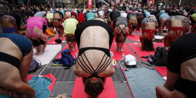 NEW YORK, NY - JUNE 21:  People do yoga in Times Square as part of the International Day of Yoga celebration on the Summer Solstice June 21, 2015 in New York City. 192 countries joined in for a mass yoga session to mark the United Nations declared, International Yoga Day.  (Photo by Kena Betancur/Getty Images)