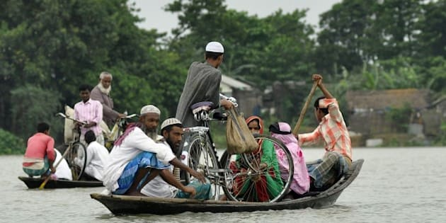 Indian villagers use a boat to travel through floodwater in Pokoriya village, some 75 kms from Guwahati on June 11, 2015. Flooding in India's northeastern state of Assam has reportedly affected some 550 villages in 14 districts, destroying crops and killing at least three people. AFP PHOTO / Biju Boro        (Photo credit should read BIJU BORO/AFP/Getty Images)