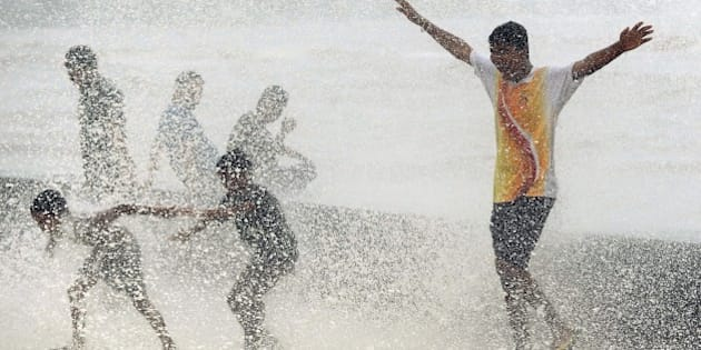 Indian youths play in breaking waves on the seafront during high tide in Mumbai on June 17, 2015. AFP PHOTO/ PUNIT PARANJPE        (Photo credit should read PUNIT PARANJPE/AFP/Getty Images)