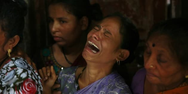 A relative of Lata Jadhav, one among the dozens who died after drinking tainted liquor, cries during her funeral in Mumbai, India, Sunday, June 21, 2015. Deaths from illegally brewed alcohol are common in India because the poor cannot afford licensed liquor. Illicit liquor is often spiked with chemicals such as pesticides to increase its potency. (AP Photo/Rafiq Maqbool)