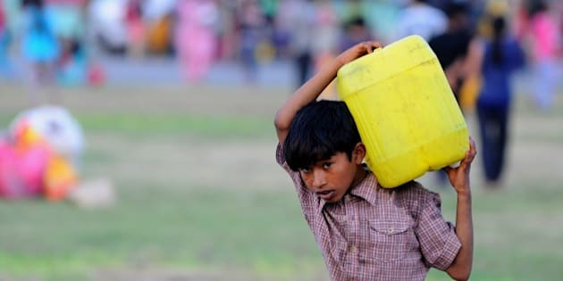 A Nepalese child carries a water can at a relief camp for survivors of the Nepal earthquake in Kathmandu on May 20, 2015. Nearly 8,500 people have now been confirmed dead in the disaster, which destroyed more than half a million homes and left huge numbers of people without shelter with just weeks to go until the monsoon rains. AFP PHOTO / ISHARA S. KODIKARA        (Photo credit should read Ishara S.KODIKARA/AFP/Getty Images)