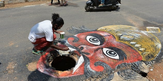 Indian artist Badal Nanjundaswamy uses the opening of an unattended manhole in the middle of a road as a canvas to depict the Hindu God of death 'Yama' waiting to gobble up unwary pedestrains or motorists  in Bangalore on June 6, 2014. The art installation was executed to draw the attention of the responsible municipal authorities into fixing the civic problem in an artistic way.  AFP PHOTO/Manjunath KIRAN        (Photo credit should read Manjunath Kiran/AFP/Getty Images)