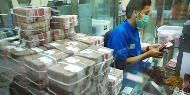 Employees of BNI bank, an Indonesian state-owned bank, prepare rupiah banknotes for their ATMs and branch offices in Jakarta on April 1, 2015. Indonesia's Central Bank had warned that the risk of losses due to the currency exchange rate of private and state-owned companies' foreign debts are still high and continue to haunt throughout 2015. AFP PHOTO / Bay ISMOYO        (Photo credit should read BAY ISMOYO/AFP/Getty Images)